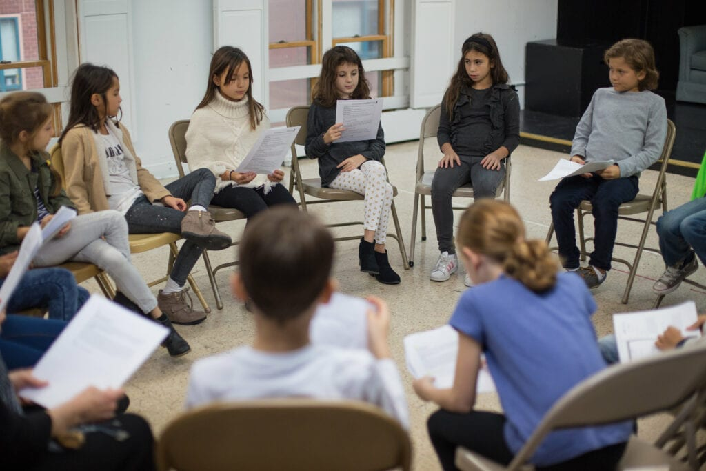 A group of young actors sit in a circle studying scripts