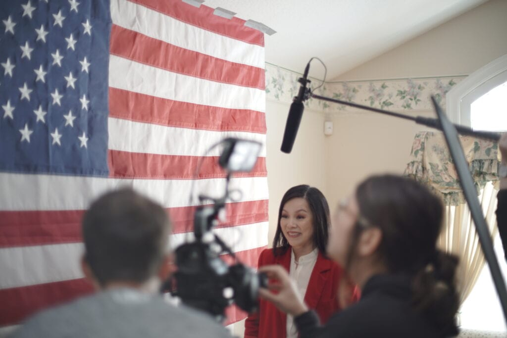 Leah Zhang with crew members around her and an American Flag on set behind.